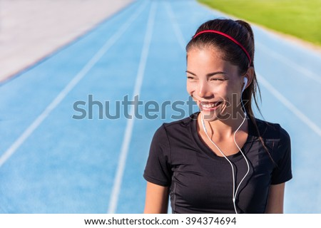 Happy track running girl runner listening to music motivation with earphones getting ready for cardio training run on blue lane athletic tracks in stadium campus. Healthy Asian athlete. - stock photo