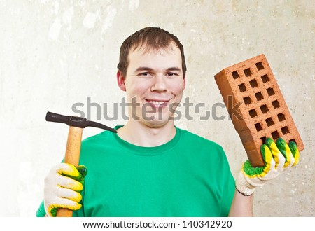 happy tradesman holding a brick and trowel - stock photo