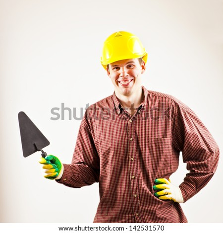 happy tradesman in a red plaid shirt holding a brick and trowel  on gray background - stock photo