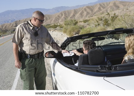Happy traffic policeman checking man's license - stock photo