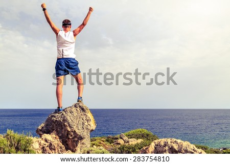Happy trail runner success achievement running or hiking accomplishment business concept with man looking over ocean horizon celebrating with arms up raised outstretched cross country running outdoors - stock photo