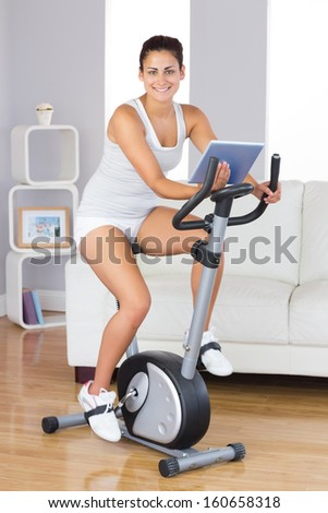 Happy training woman using an exercise bike while holding a tablet in her living room - stock photo
