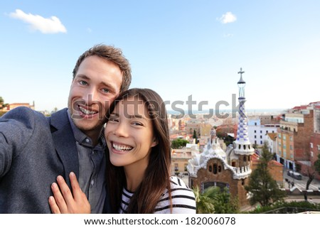 Happy travel couple in Park Guell, Barcelona, Spain. Beautiful young multiracial couple looking at camera taking selfie smiling happy having fun on Europe vacation trip. Asian woman, Caucasian man. - stock photo