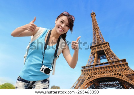 Happy travel woman in Paris with Eiffel Tower and she show thumb up, asian beauty - stock photo
