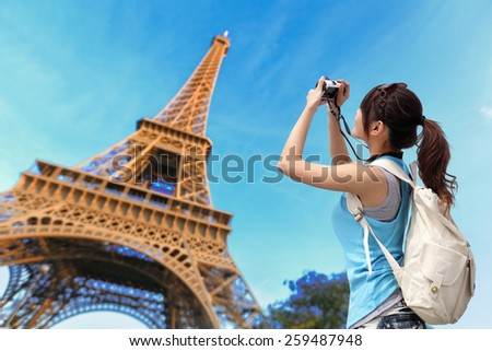 Happy travel woman in Paris with Eiffel Tower and she take a picture, asian beauty - stock photo