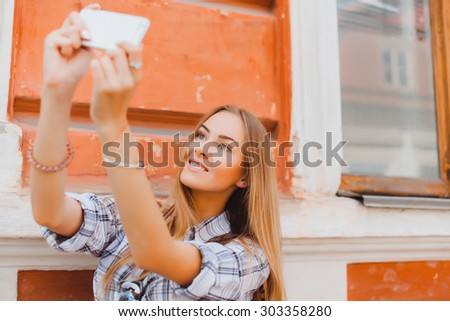 Happy travel young girl selfie taking pictures of herself isolated over white background, Fashionable attractive woman taking a self portrait. Selfie, indoor, horizontal, over white wall - stock photo