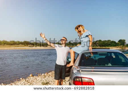 Happy traveler couple hugging a car by the river to the sunrise