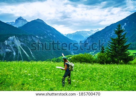 Happy traveler in the mountains, active woman searching right way on the map, travel to Alpine mountain, journey and adventure concept - stock photo