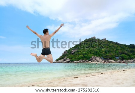 Happy traveler jumping on the beach, ko nangyuan, THAILAND. - stock photo