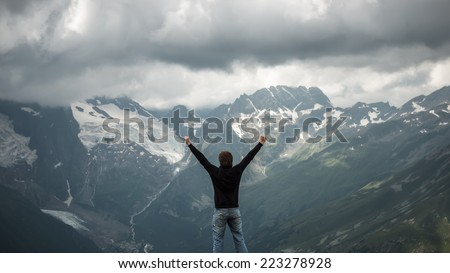 happy traveler on the top of mountain stormy landscape - stock photo
