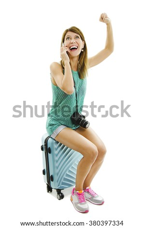 Happy traveler, sitting on a suitcase talk on smart phone with good news. Isolated on white background - stock photo