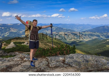 Happy traveler standing on a rock with backpack with raised hands on the background of autumn mountains. - stock photo
