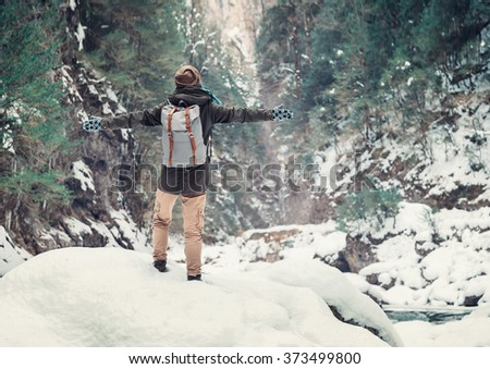 Happy traveler young woman with backpack standing with raised arms and enjoying a beautiful nature in winter - stock photo