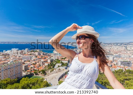 Happy traveling! Pretty girl in a hat and sunglasses posing against the city of Marseille - stock photo