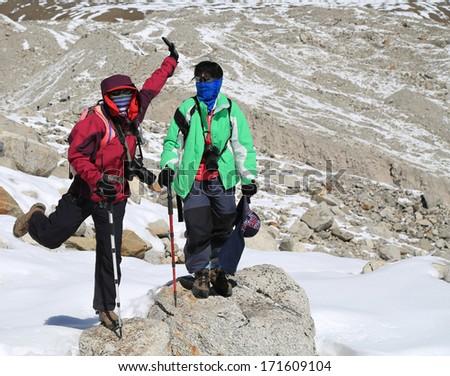 happy trekker acting from everest trek route in nepal - stock photo