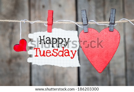 Happy Tuesday on instant paper and small red hearts hanging on the clothesline. On old wood background - stock photo