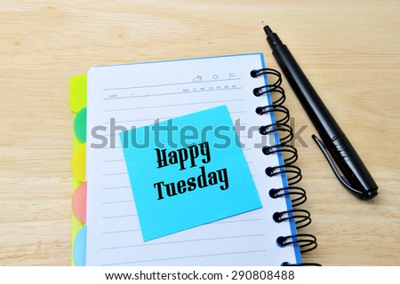 Happy Tuesday words written on a blue sticky note pinned, notebook with pan on wooden background - stock photo
