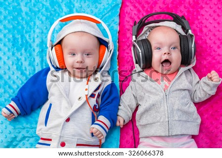 Happy twin babies listening to the music on headphones - stock photo