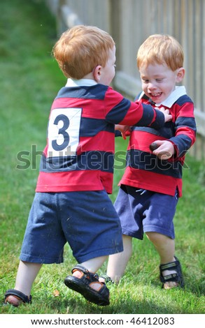 Happy twin boys wearing rugby shirts