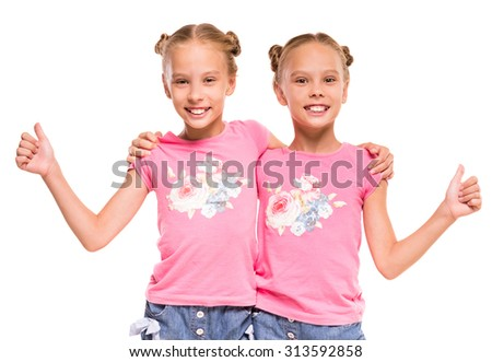 Happy twins embracing each other and showing thumbs up, isolated on white background. - stock photo