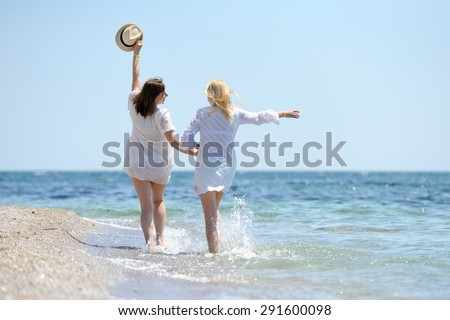 Happy two beautiful womans in white dress running on the beach - stock photo