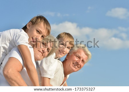 Happy two brothers and their grandparents against the sky