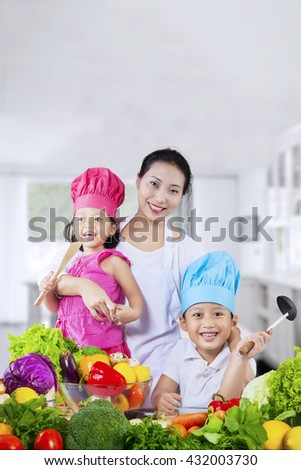 Happy two children with their mother preparing fresh vegetables in the kitchen at home