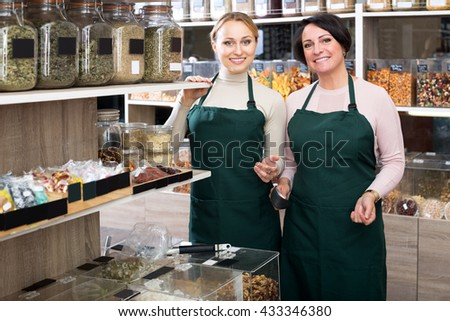 Happy two female sellers wearing apron and standing next to organic foods in the bio-store
