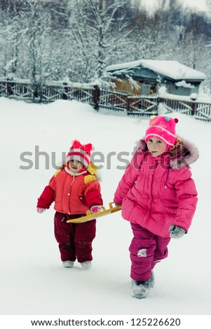 Happy two girl in red clothes in winter outdoors