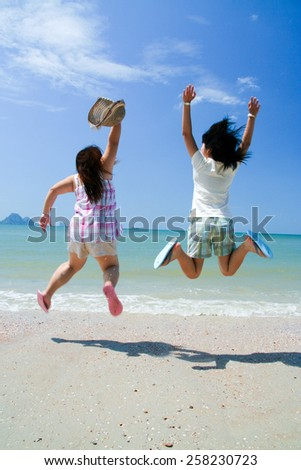 Happy two girl jumping over sea.