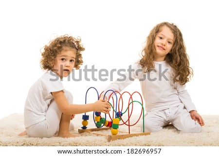 Happy two girls playing with wooden toy home and sitting together on fur carpet