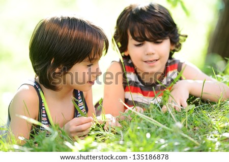 Happy two little boys outdoors in nature having good time - stock photo