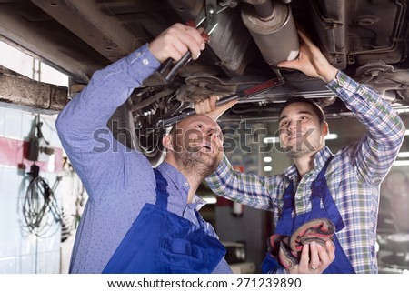 Happy two male workers in overalls working in the garage. Focus on the left man - stock photo