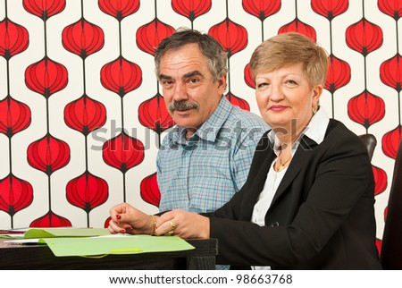 Happy two mature people in modern office having meeting - stock photo