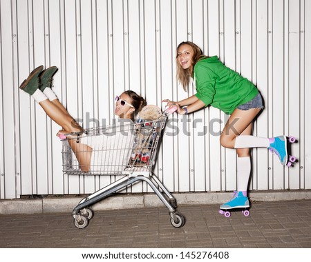 Happy two naughty women with shopping cart. outdoors - stock photo