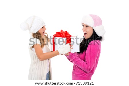 happy two teenage girl smile, presenting, giving gift box looking to each other, wear warm winter hat over white background