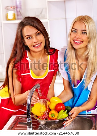 Happy two women preparing food at kitchen. - stock photo