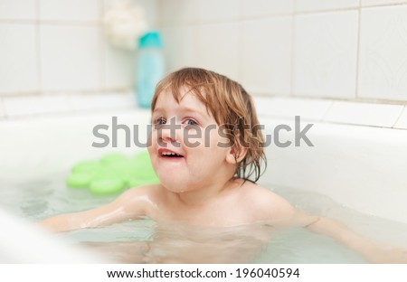 Happy two-year child bathes with toys in bathtub
