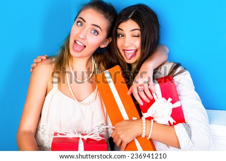 Happy two young girls friends just getting their presents, having fun and showing tongue . Bright colors blue background. - stock photo