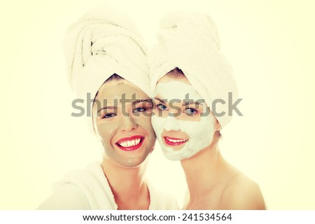 Happy two young woman with anti-aging masks - stock photo