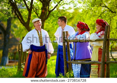 happy ukrainian family in traditional costumes talking near the country house - stock photo