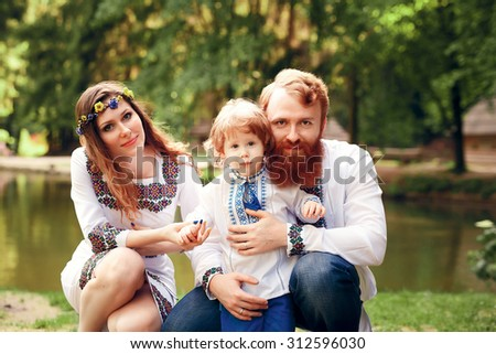 Happy ukrainian family with little son in traditional ukrainian dress in a countryside, park
