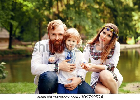 Happy ukrainian family with little son in traditional ukrainian dress in a countryside, park. Look at camera. Father, mother, son.