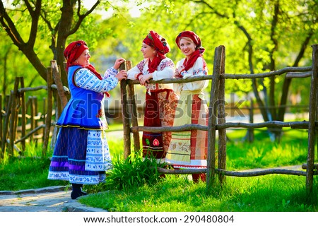 happy ukrainian women, dressed in traditional costumes, talking on the street - stock photo