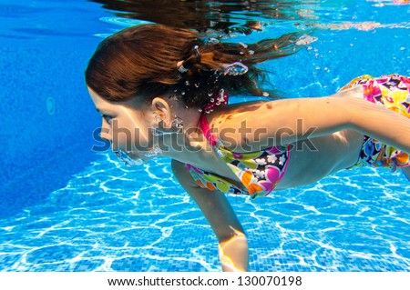 Happy underwater child in swimming pool, beautiful girl swims and having fun. Kids sport on family summer vacation. Active healthy holiday
