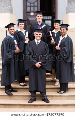 happy university professor and group of graduates at graduation ceremony - stock photo