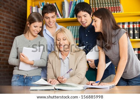 Happy university teacher with book explaining students in library