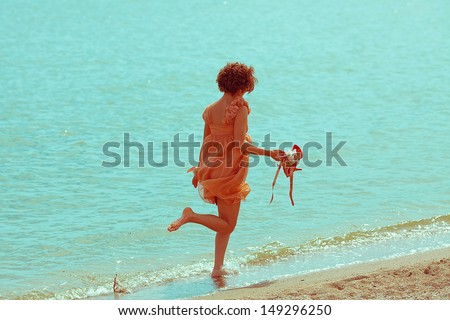 Happy vacation concept. Young girl walking (running) along the beach and holding her shoes. Sunny summer day. Copy-space. Outdoor shot