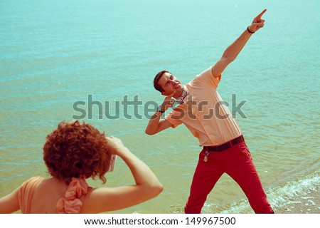 Happy vacation concept. Young happy married hipsters in trendy vintage clothes making photographs (pictures) on the beach. Sunny summer day. Retro style. Copy-space. Outdoor shot - stock photo