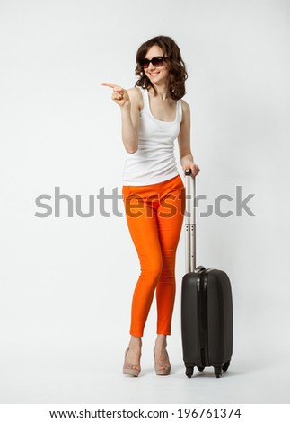Happy vacation! Playful smiling young woman in orange pants with suitcase on neutral background - stock photo